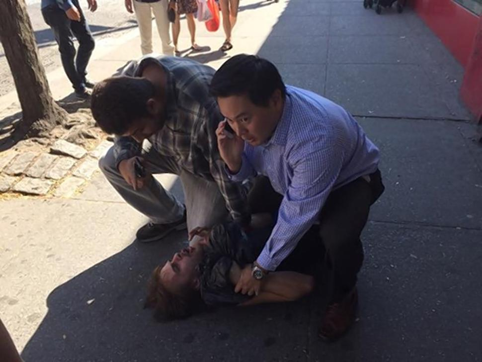 New York State Assemblyman Ron Kim holds down a purse snatcher Thursday in downtown Flushing after tackling the thief.