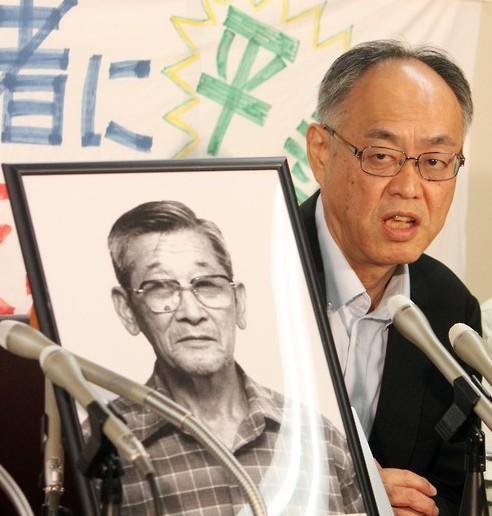 Yasuhisa Nagashima, a lawyer for South Korean victims of the U.S. 1945 atomic bombing of the two Japanese cities, Hiroshima and Nagasaki, holds a press conference in Tokyo on Sept. 8, 2015, after Japan's highest court ruled that South Korean atomic bomb victims residing in their homeland are entitled to full compensation from local authorities in Japan. Next to him is a framed photo of Kang Sung-joon, a diseased South Korean victim of the bombing. (Yonhap)