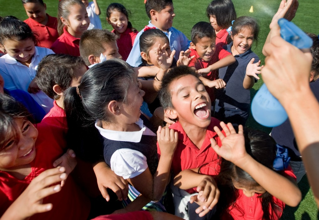 Students enjoy a cool spray of water while on the playground with classmates at Garfield Elementary School in Santa Ana, Calif. on Wednesday, Sept. 9, 2015. (Mindy Schauer/The Orange County Register via AP)