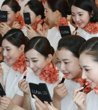 A group of newly-hired flight attendants puts on lipstick during a makeup training session at an office of Jeju Air Co., South Korea's top budget carrier, in Seoul on Sept. 9, 2015. The session is part of a training program that new employees are required to go through. (Yonhap)