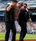 Pittsburgh Pirates' Jung Ho Kang, center, is helped off the field by a team trainer, right, and his interpreter after injuring his left leg turning a double play in the first inning of a baseball game against the Chicago Cubs in Pittsburgh, Thursday, Sept. 17, 2015. Kang left the game. (AP Photo/Gene J. Puskar)