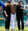 Pittsburgh Pirates' Kang Jung-ho, center, is helped off the field by a team trainer, right, and his interpreter after injuring his left leg turning a double play in the first inning of a baseball game against the Chicago Cubs in Pittsburgh, Thursday, Sept. 17, 2015. Kang left the game. (AP Photo/Gene J. Puskar)