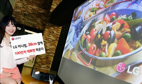 A model poses for a photo with the latest projector released by LG Electronics Inc. on Sept. 10, 2015. LG said the device needs a distance of only 38 centimeters to display a 254 cm screen on the wall, reducing the required space by a tenth. (Yonhap)