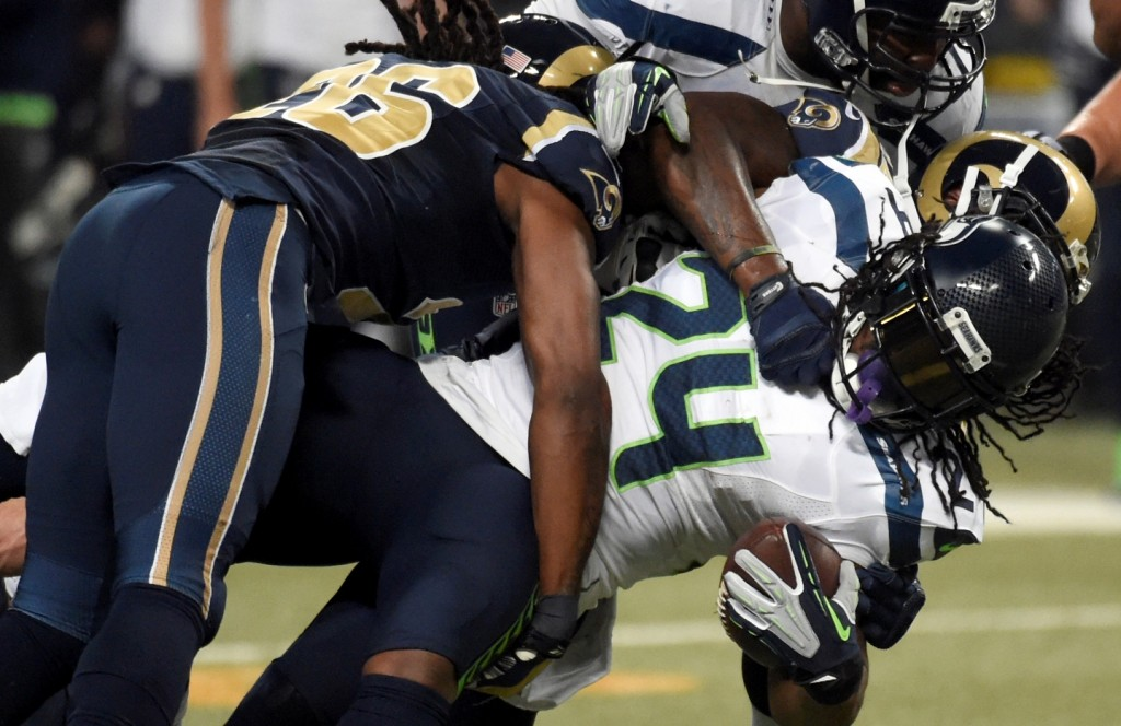 Seattle Seahawks running back Marshawn Lynch, right, struggles for yardage before being brought down by St. Louis Rams strong safety Mark Barron, left, during the first quarter of an NFL football game Sunday, Sept. 13, 2015, in St. Louis. (AP Photo/L.G. Patterson)