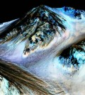 This undated photo provided by NASA and taken by an instrument aboard the agency's Mars Reconnaissance Orbiter shows dark, narrow, 100 meter-long streaks on the surface of Mars that scientists believe were caused by flowing streams of salty water. Researchers said Monday, Sept. 28, 2015, that the latest observations strongly support the longtime theory that salt water in liquid form flows down certain Martian slopes each summer. (NASA/JPL/University of Arizona via AP)