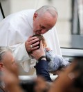 Pope Francis passes the crowd and kisses a baby in his pope mobile in Philadelphia on Saturday, Sept. 26, 2015. The pope spoke at Independence Hall on his first visit to the United States. (Jim Bourg/Pool Photo via AP)