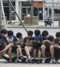 South Korean high school students play games on their smartphones on a bench on the sidewalk in Seoul, South Korea. Security researchers say they found critical weaknesses in a South Korean government-mandated child surveillance app, vulnerabilities that could have allowed hackers to easily violate the private lives of the country's youngest citizens. (AP Photo/Ahn Young-joon, File)