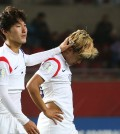 Lee Seung-woo, right, and Lee Sang-min walk off the field after a disappointing loss to Belgium. (Yonhap)