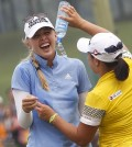 Jessica Korda, left, of the United States is poured water by fellow golfer Ha Na Jang of South Korea after winning the LPGA Malaysia golf tournament at Kuala Lumpur Golf and Country Club in Kuala Lumpur, Malaysia, Sunday, Oct. 11, 2015.(AP Photo/Joshua Paul)