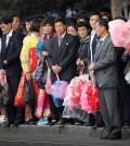 North Koreans carry decorative flowers to be used during upcoming anniversary celebrations while waiting at a city trolley stop, Thursday, Oct. 8, 2015, in Pyongyang, North Korea. The country is in high gear with preparations for the 70th anniversary of the founding of North Korea's Workers' Party on Oct. 10, 2015. (AP Photo/Wong Maye-E)