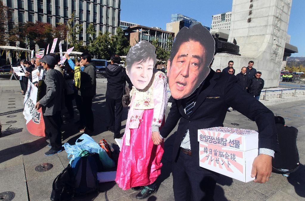 Protesters wearing masks of Japanese Prime Minister Shinzo Abe, right, and South Korean President Park Geun-hye prepare to join in a rally against Abe's planned visit in Seoul, South Korea, Friday, Oct. 30, 2015. Abe and Chinese Premier Li Keqiang will visit Seoul for their trilateral summit with Park. (AP Photo/Ahn Young-joon)