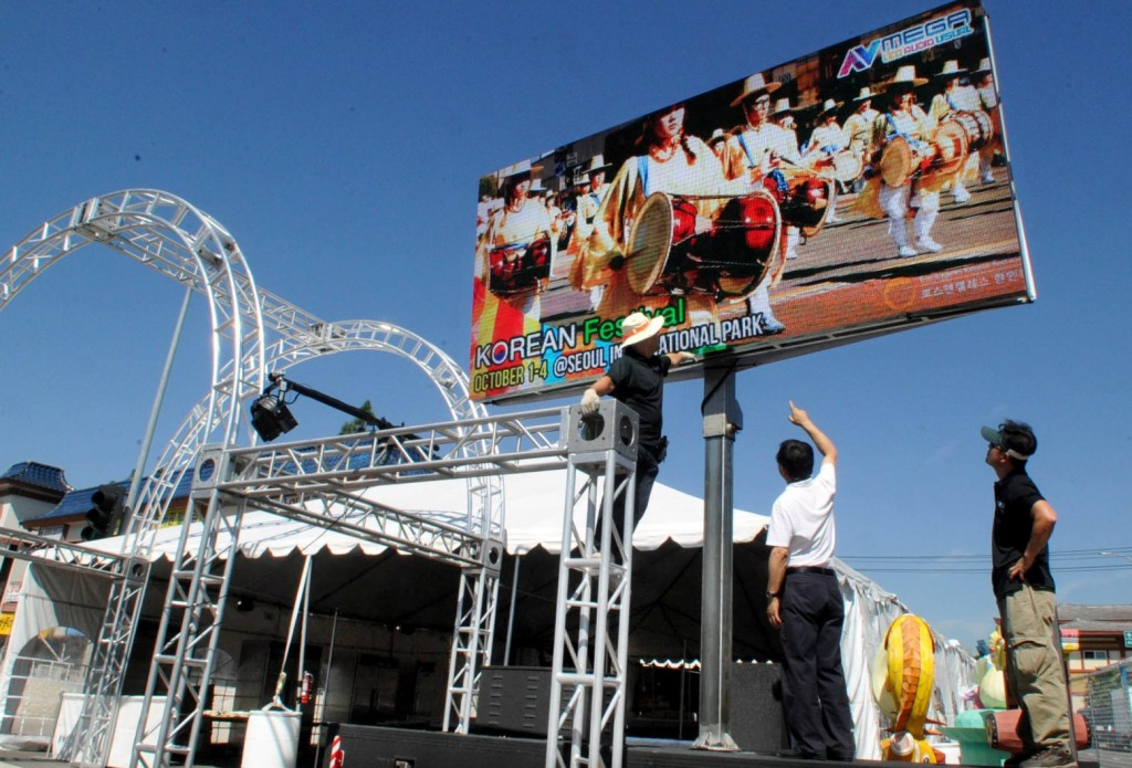 Los Angeles Korean Festival Foundation staff install an LED billboard for the festival Wednesday at the entrance of Seoul International Park. (Park Sang-hyuk/Korea Times)