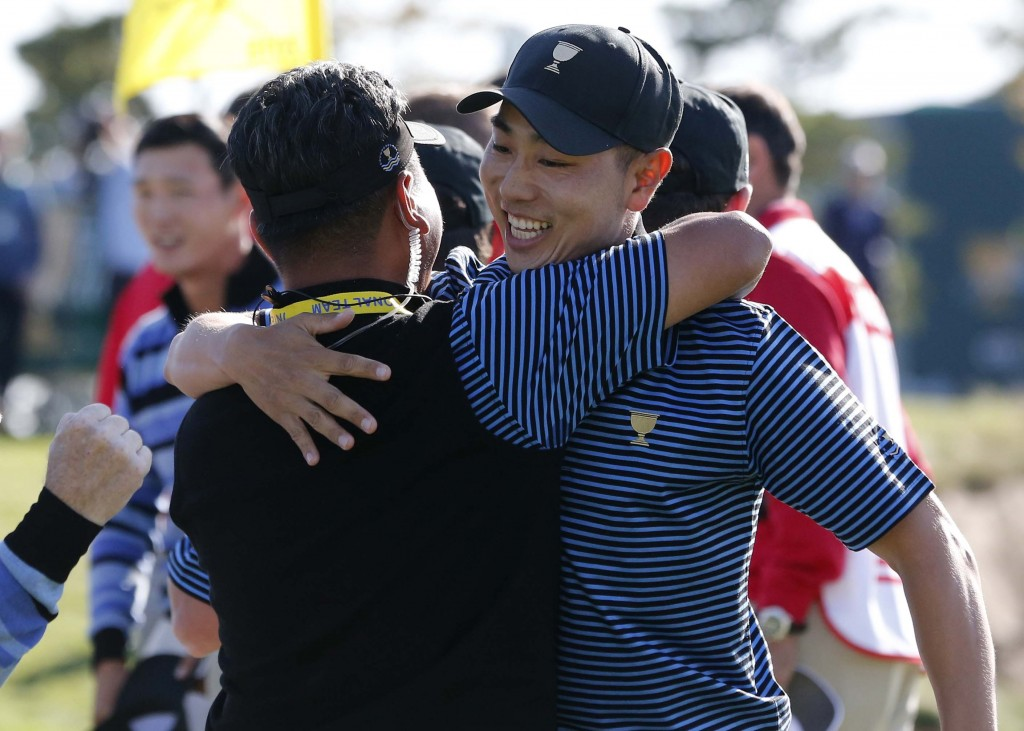 International team player Bae Sang-moon, right, of South Korea is embraced by compatriot and team vice captain K.J.Choi after winning their four ball match at the Presidents Cup golf tournament at the Jack Nicklaus Golf Club Korea, in Incheon, South Korea, Friday, Oct. 9, 2015.(AP Photo/Lee Jin-man)