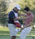 Bae Sang-Moon of South Korea, right, is greeted by his caddy and spray from sparkling wine on the 18th green of the Silverado Resort North Course after winning the Frys.com PGA Tour golf tournament Sunday, Oct. 12, 2014, in Napa, Calif. Bae Sang-Moon won the tournament after shooting a 1-over-par 73 to finish at total 15-under-par. (AP Photo/Eric Risberg)