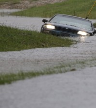 A car is submerged in floodwaters in Florence, S.C., Sunday, Oct. 4, 2015 after steady rain left many roads impassable, while flooding continues in many parts of the state. (AP Photo/Gerry Broome)