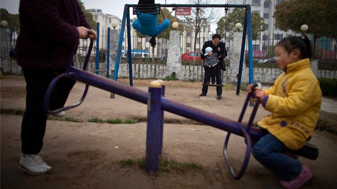 In this April 5, 2010 file hoto, Chinese grandparents and grandchildren play in a park in Dafeng, in east China's Jiangsu province. China's ruling Communist Party announced Thursday, Oct. 29, 2015, that it will abolish the country's decades-old one-child policy and allow all couples to have two children, removing remaining restrictions that limited many urban couples to only one, the official Xinhua News Agency said. (AP Photo/Alexander F. Yuan, file)