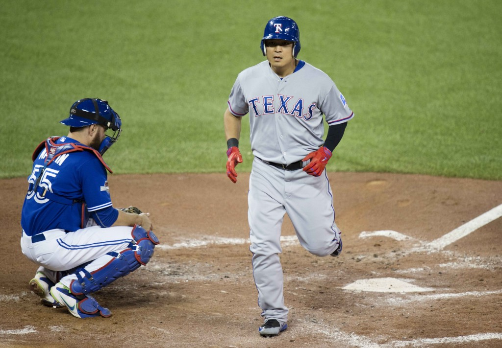 Texas Rangers' Choo Shin-soo, right, crosses home plate in front of Toronto Blue Jays catcher Russell Martin following a solo home run during the third inning in Game 5 of baseball's American League Division Series, Wednesday, Oct. 14, 2015 in Toronto. (Darren Calabrese/The Canadian Press via AP)