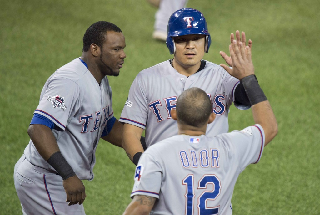 Texas Rangers, from left to right, Hanser Alberto, Choo Shin-soo, and Rougned Odor celebrate Choo scoring during the first inning in Game 2 of baseballs American League Division Series in Toronto on Friday, Oct. 9, 2015. (Darren Calabrese/The Canadian Press via AP)