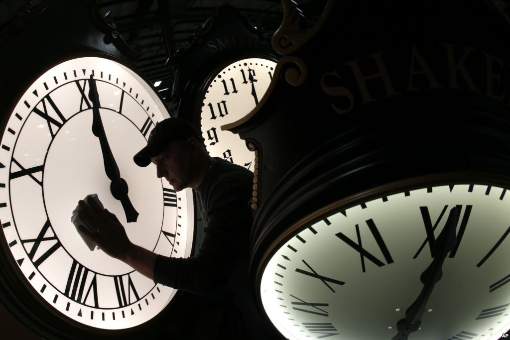 Dave LeMote wipes down a post clock at Electric Time Company, Inc. in Medfield, Mass. Most Americans will set their clocks 60 minutes back before heading to bed Saturday night, but daylight saving time officially ends Sunday at 2 a.m. local time. (AP Photo/Elise Amendola)