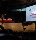 A video show the impact of a missile on Malaysia Airline Flight 17, while a part of the reconstructed forward section of the fuselage is displayed behind, as Tjibbe Joustra, left, head of the Dutch Safety Board presents the board's final report into what caused Malaysia Airlines Flight 17 to break up high over Eastern Ukraine last year, killing all 298 people on board, during a press conference in Gilze-Rijen, central Netherlands, Tuesday, Oct. 13, 2015. (AP Photo/Peter Dejong)