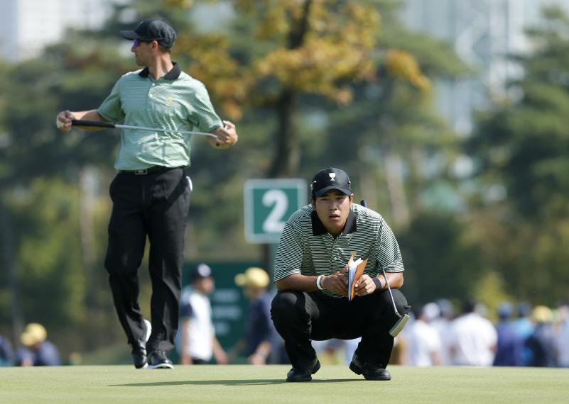 International team player Hedeki Matsuyama, right, of Japan and teammate Adam Scott of Australia prepare to putt during their foursome match at the Presidents Cup golf tournament at the Jack Nicklaus Golf Club Korea, in Incheon, South Korea, Thursday, Oct. 8, 2015.(AP Photo/Woohae Cho)