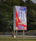 In this Sept. 15, 2015, photo, people walk past a sign board marking the upcoming 70th anniversary of the founding of North Korea's Workers' Party in Pyongyang, North Korea. While North Korea prepares a big show to mark the 70th anniversary of the ruling Workers' Party, the daily struggles of life outside the capital - such as finding clean running water and putting nutritious food on the table year-round - pose a harsh, but largely unseen, contrast to the grand celebrations the world will see Oct. 10. (AP Photo/Wong Maye-E)