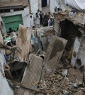 People stand outside a house damaged from an earthquake in Peshawar, Pakistan, Monday, Oct. 26, 2015. A powerful 7.7-magnitude earthquake in northern Afghanistan rocked cities across South Asia. Strong tremors were felt in Kabul, New Delhi and Islamabad on Monday. In the Pakistani capital, walls swayed back and forth and people poured out of office buildings in a panic, reciting verses from the Quran. (AP Photo/Mohammad Sajjad)