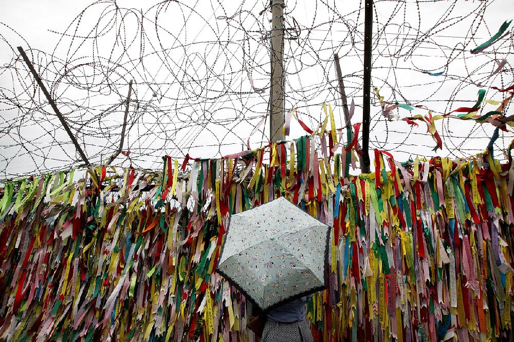 A visitor reads messages on ribbons wishing for the reunification of the two Koreas at the Imjingak Pavilion near the border village of Panmunjom, which has separated the two Koreas since the Korean War, in Paju, South Korea, Tuesday, Aug. 25, 2015. After more than 40 hours of talks, North and South Korea pulled back from the brink Tuesday with an accord that allows both sides to save face and, for the moment, avert the bloodshed they've been threatening each other with for weeks.(AP Photo/Ahn Young-joon)