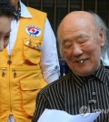South Korean resident Kim Woo-jong (R), 87, learns he was included in the final list of family members separated by the 1950-53 Korean War to join the upcoming reunions, as he meets with Kim Sung-joo, South Korea`s Red Cross chief, at his house in Seoul on Oct. 8, 2015. The relief group handed over a list of 90 South Koreans hoping to meet their relatives living in North Korea while the North delivered a list of 97 North Korean family members to the South. (Yonhap)