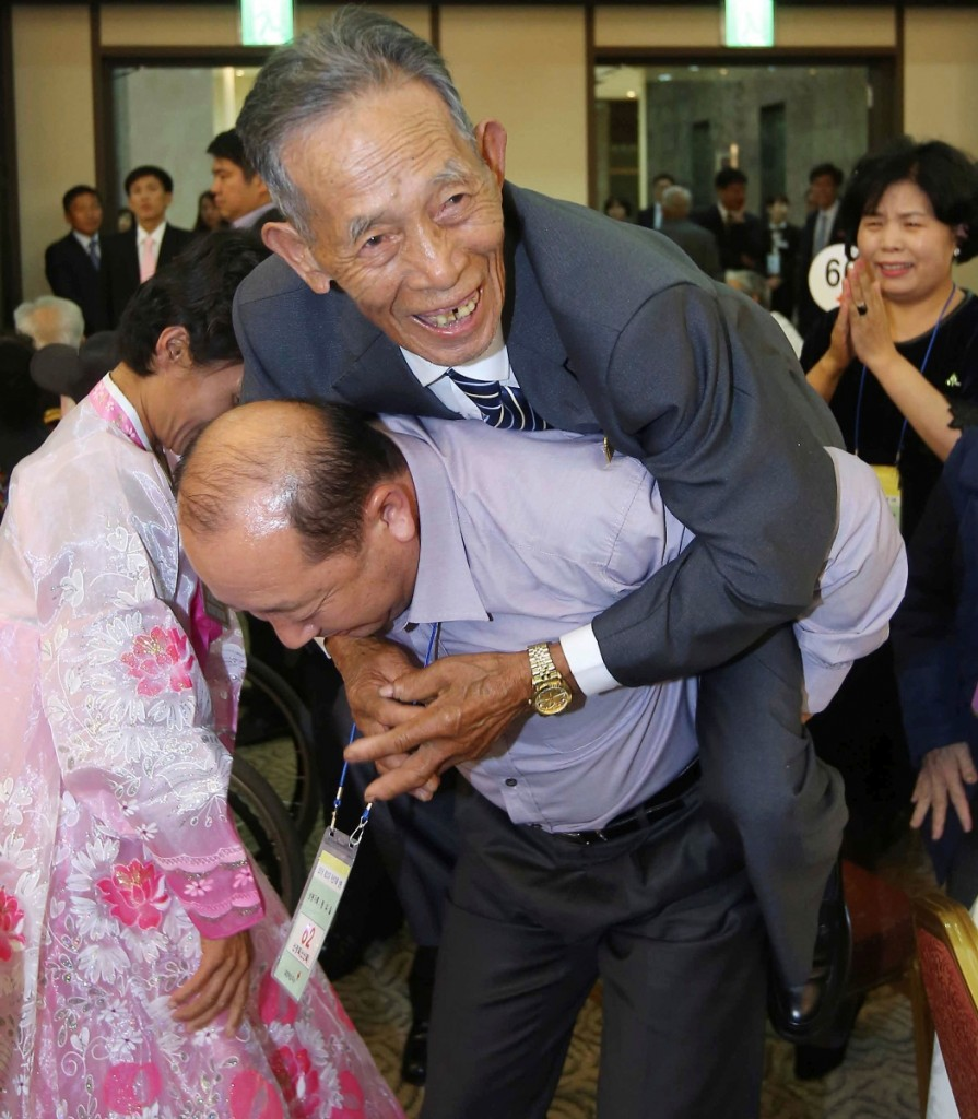North Korean family member Sin Kyong Muk, 82, is carried by his South Korean niece's husband Jeong Wu-il, 55, on his back during the Separated Family Reunion Meeting at Diamond Mountain resort in North Korea, Wednesday, Oct. 21, 2015. Hundreds of elderly Koreans from divided North and South began three days of reunions Tuesday with loved ones many have had no contact with since the war between the countries more than 60 years ago. (Kim Do-hoon/Yonhap via AP)