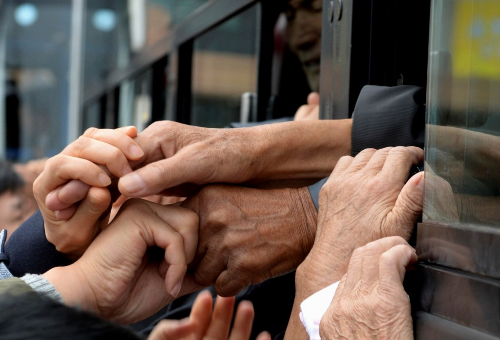 South Koreans and their North Korean relatives on a bus grip their hands each other to bid farewell after the Separated Family Reunion Meeting at Diamond Mountain resort in North Korea, Thursday, Oct. 22, 2015. Hundreds of elderly Koreans are weeping and embracing as they part — perhaps for good — after briefly reuniting for the first time in more than 60 years. About 390 South Koreans traveled to the North's scenic Diamond mountain resort earlier this week to meet for three days with relatives they were separated from during the turmoil of the 1950-53 Korean War. (Korea Pool Photo via AP)