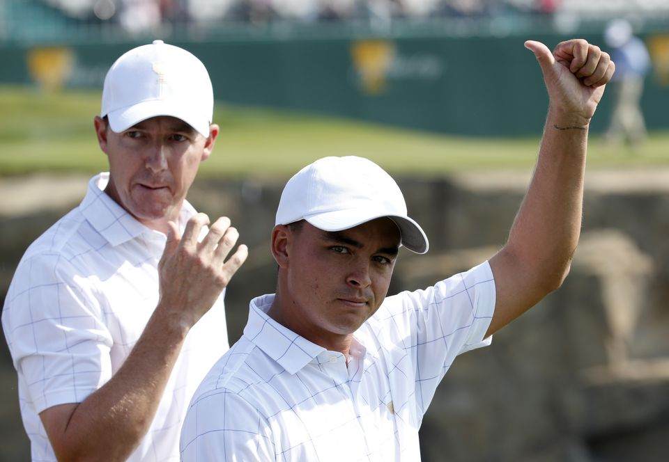 United States' Rickie Fowler gestures to the crowd as he walks with teammate Jimmy Walker during their foursome match at the Presidents Cup golf tournament at the Jack Nicklaus Golf Club Korea, in Incheon, South Korea, Thursday, Oct. 8, 2015.(AP Photo/Lee Jin-man)