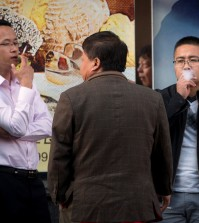In this Thursday, Oct. 8, 2015 photo, men smoke cigarettes outside of an office building in Beijing. Research published in the medical journal The Lancet says one in three of all the young men in China are likely to die from tobacco, but that the number can fall if the men quit smoking. (AP Photo/Mark Schiefelbein)