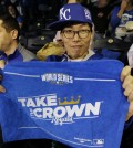Kansas City Royals fan Lee Sung-woo, from South Korea, shows off a World Series towel before Game 1 of baseball's World Series between the Kansas City Royals and the San Francisco Giants Tuesday, Oct. 21, 2014, in Kansas City, Mo. (AP Photo/Charlie Neibergall)