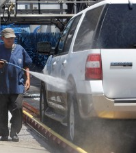 In this June 24, 2015, file photo, a worker washes a car at Bob's Car Wash in Roseville, Calif. To reduce water use, owner Nancy van Overbeek says the facility had upgraded its recycling and reclamation system and was not watering its lawn. State officials plan to tell Californians what penalties they are taking against communities that fail to meet a mandated 25 percent reduction in water use when they announce usage figures Friday, Oct. 30, in the state's battle against a widespread drought. (AP Photo/Rich Pedroncelli, File)