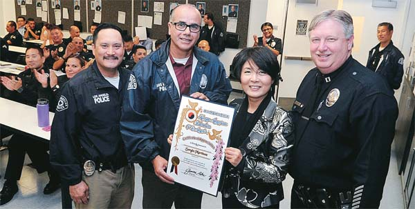 Laura Jeon, a KAFLA leader, second from right, presents a certificate of gratitude to LAPD Olympic Division Detective Sergio Martinez Wednesday. (Park Sang-hyuk/Korea Times)