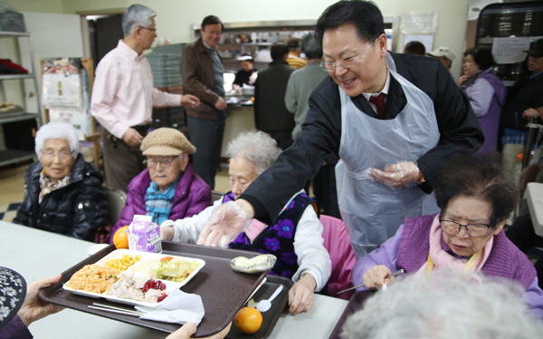 Yoo Dae-geun, president of the New York Korean American Supermarkets Association, helps hand out free Thanksgiving meals to seniors Wednesday.