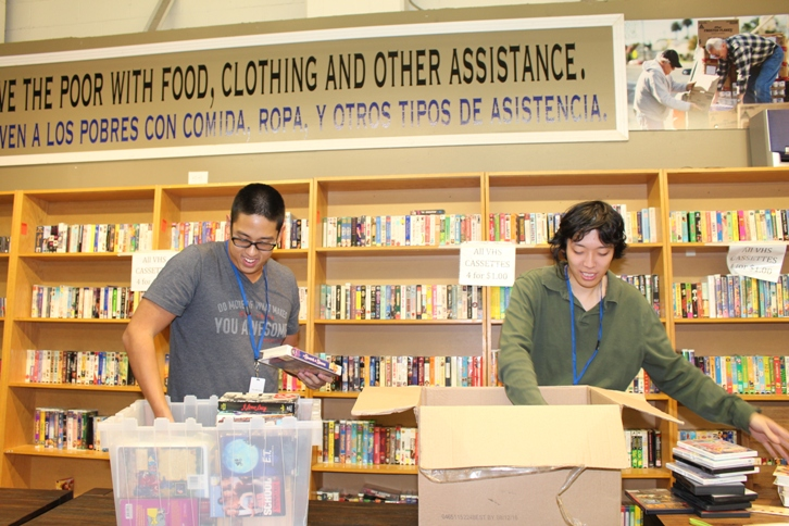 Volunteers Albert Lee, left, and Eugene Moon, right, of Fortes in Fide unload and shelve used VHS and DVD movies at St. Vincent de Paul Thrift Store in downtown L.A. (Courtesy of St. Vincent de Paul of Los Angeles / Kay Hwangbo)