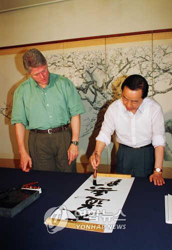 South Korean President Kim Young-sam, right, writes a banner to gift to U.S. President Bill Clinton, left, during Clinton's visit to South Korea on July 11, 1993. (Yonhap)