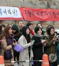 Fans of TVXQ's Chang-min and Super Junor's Si-won wait outside a Chungnam base Thursday morning to say goodbye before the two stars enlist in their 21-month military service. (Yonhap)