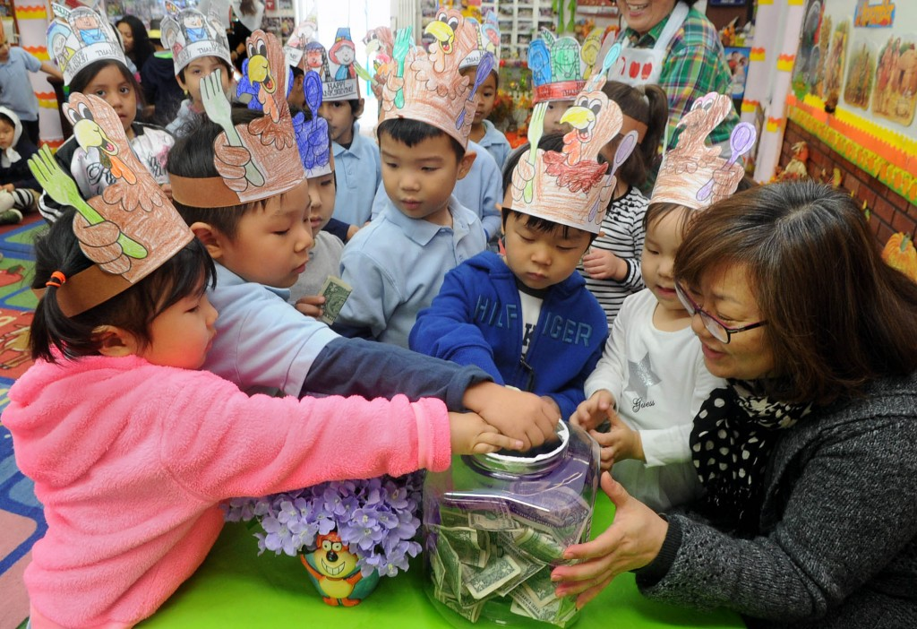 Children wearing turkey hats at Lily Preschool and Kindergarten in Los Angeles put money in a donation jar to help the kids who live on the streets of India. (Park Sang-hyuk)
