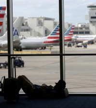 A traveler rests on the floor as American Airlines aircraft are lined up the the gates at Miami International Airport, Tuesday, Nov. 24, 2015, in Miami. Thanksgiving is one of the busiest travel holidays of the year, both in the air and on the roads. (AP Photo/Lynne Sladky)