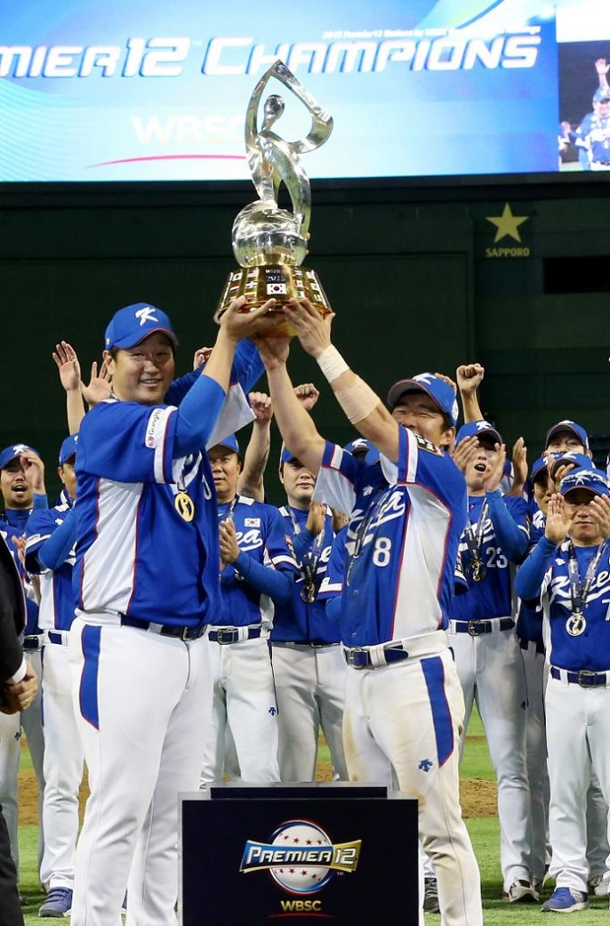 South Korea's Lee Dae-ho (L) and Jeong Keun-woo hold up the trophy as they celebrate after defeating the United States in the final of WBSC Premier 12 baseball tournament at Tokyo Dome in the Japanese capital on Nov. 21, 2015. South Korea won the match 8-0 to become the inaugural champion of the tournament. (Yonhap)