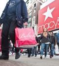 Shoppers carry bags as they cross a pedestrian walkway near Macy's in Herald Square, Friday, Nov. 27, 2015, in New York. The early numbers aren't available yet on how many shoppers headed out to stores on Thanksgiving, instead of waiting until today. But it's expected that more than three times the number who shopped yesterday will be out bargain-hunting today.(AP Photo/Bebeto Matthews)