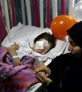 FILE - In this Friday, Nov. 13, 2015 file photo, Adraa Taleb holds the hand of her maternal cousin Haidar Mustafa, three, who was wounded in Thursday's twin suicide bombings, as he sleeps on a bed at the Rasoul Aazam Hospital in Burj al-Barajneh, southern Beirut, Lebanon. Haidar's parents Hussein and Leila were killed in the blast as they were parking their car when one of two suicide attackers blew himself up in a southern Beirut suburb near their vehicle. Within hours of the Paris attacks last week that left 129 dead, outrage and sympathy flooded social media feeds and filled the airwaves. Commenting on the public outpouring of support and anger following the Paris attacks, Lebanese blogger Joey Ayoub accused the media and world leaders of caring less about deaths in Beirut in IS attacks than deaths in Paris at the hands of the same group. (AP Photo/Bilal Hussein, File)