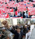 BOTTOM -- South Korean protesters shout slogans during a rally supporting the revision of the publication system for Korean history textbooks in Seoul, South Korea, Tuesday, Nov. 3, 2015. The South Korean government on Tuesday announced a switch to its current history textbook system for school students, moving from a government-authorising system to state publishing, in the midst of backlash from the public and opposition parties. (AP Photo/Ahn Young-joon)