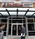 FILE - In this Nov. 9, 2015, file photo, pedestrians walk past a still-closed Chipotle restaurant in Seattle. An outbreak of E. coli that originated in the Pacific Northwest has spread south and east and has now infected people in six states. New cases have been reported in California, New York and Ohio, the Centers for Disease Control and Prevention said Friday, Nov. 20, 2015. (AP Photo/Elaine Thompson, File)