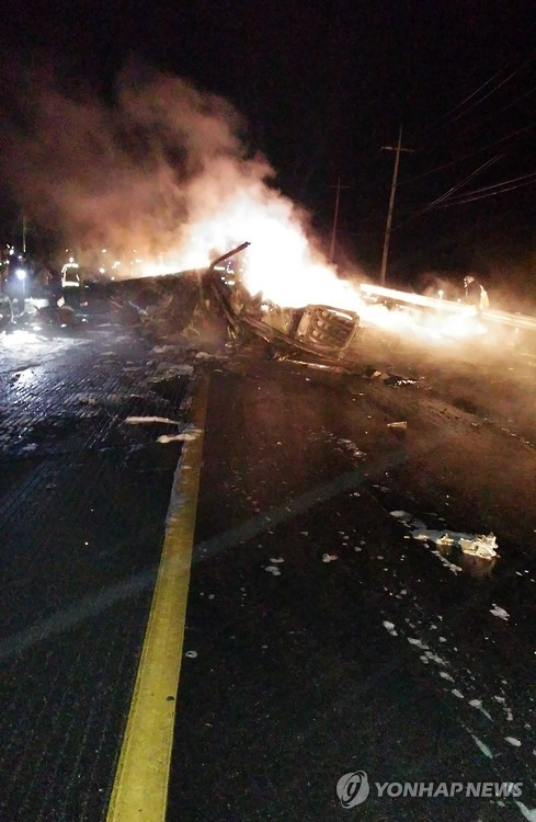 The wreckage of a U.S. military AH-64 Apache helicopter is burning along a road in Wonju, South Korea, Monday, Nov. 23, 2015. A U.S. military helicopter crashed in South Korea on Monday, killing two people on board, police said. (Park Young-suh/Yonhap)