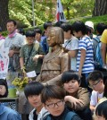 Japanese protesters stand around a comfort women memorial near the Japanese Embassy in Seoul. (Yonhap)