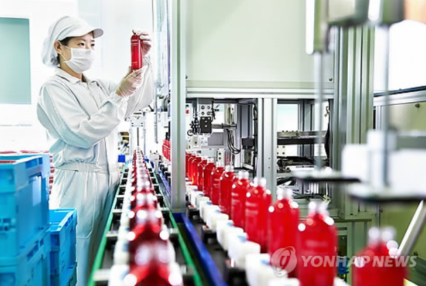An employee at Amore Pacific, a South Korean cosmetic maker, examines a sample at a factory. (Yonhap)